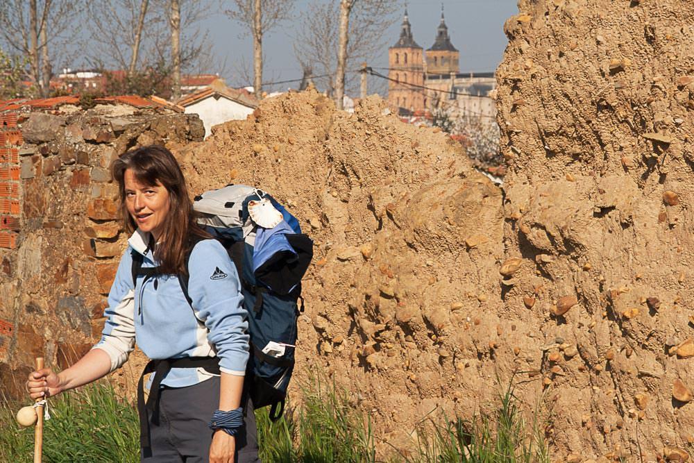 Beate Steger 2007 auf dem Jakobswg, steht vor einer Mauer, hat Rucksack auf und Pilgerstab in der Hand