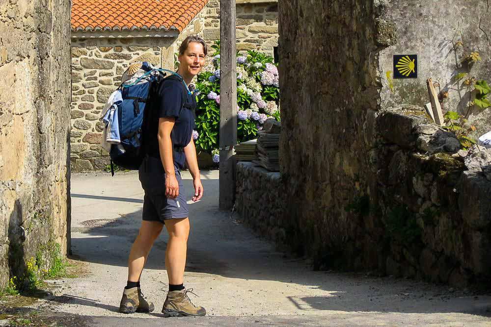 Beate Steger mit Rucksack seitlich stehend, an der Wand sieht man ein Wegzeichen des Jakobswegs