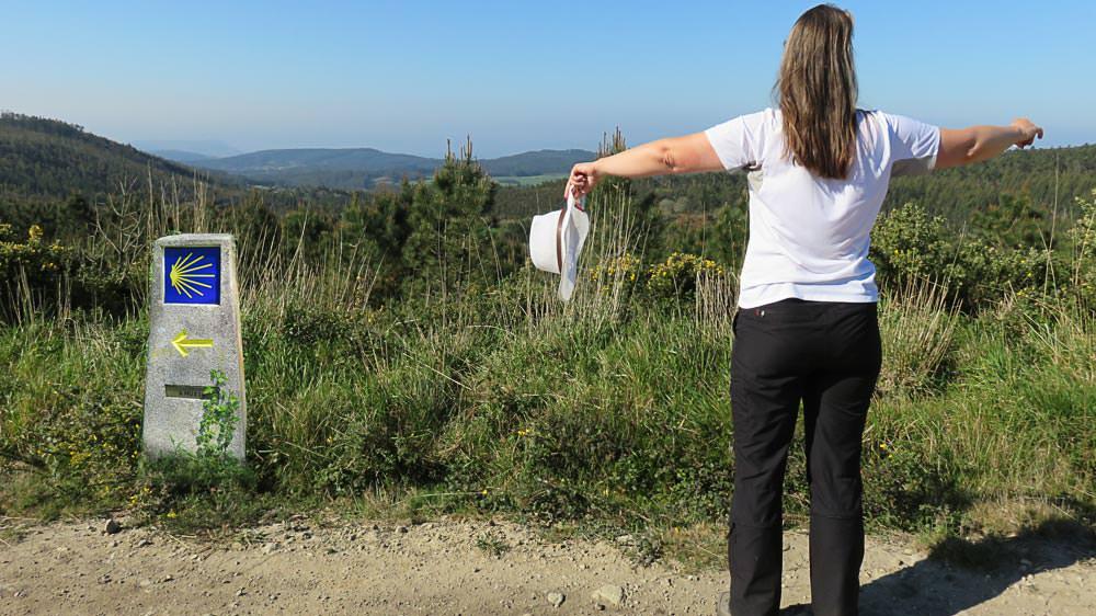 Beate Steger mit dem Rücken ohne Rucksack zu sehen, links Wegzeichen des Jakobswegs