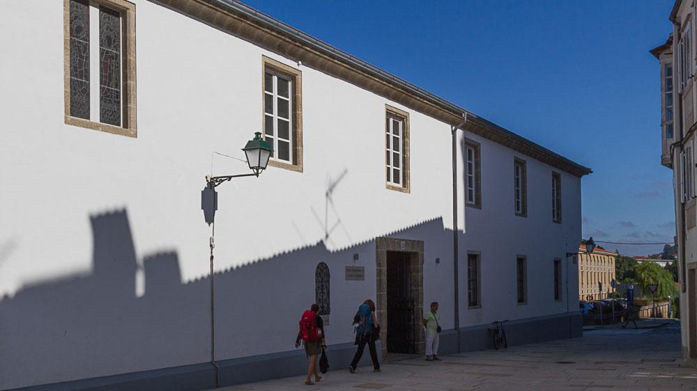 Weiß gestrichenes, langgezogenes Gebäude in Santiago, in dem jetzt das Pilgerbüro untergebracht ist