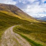Schottische Highlands mit Wanderpfad und blauem Himmel