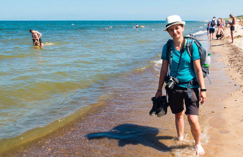 Ostsee, Sandstrand mit wenigen Leuten und Doro mit Fotoapparat und Schuhen in der Hand pilgert barfuss am Strand