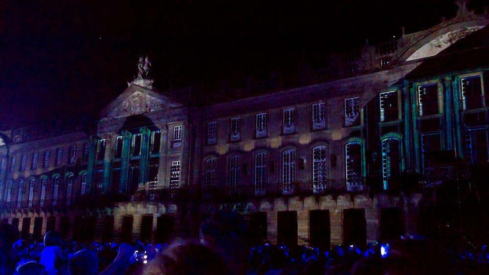 Gebäude bei Nacht mit aufprojizierten Lichtern und dunkler Menschenmenge davor