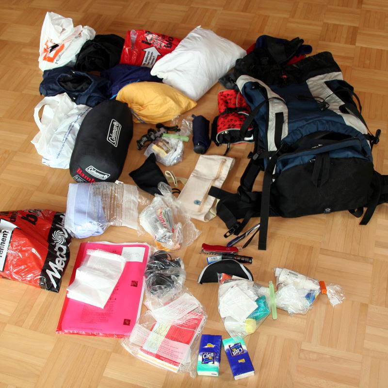 Schuhe, Kulturbeutel, Kleidung, Unterlagen, alles ordentlich in Tüten, auf dem Boden bevor es in den Rucksack kommt