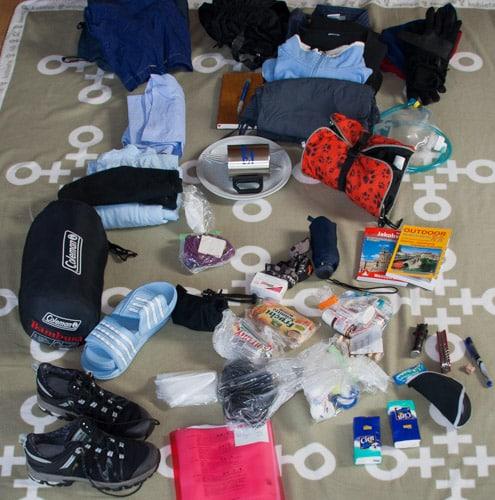 Viele Ausrüstungsgegenstände auf dem Boden wie z.B. Schlafsack, Schuhe, Rucksack, Dokumente, etc.