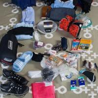viele Ausrüstungsgegenstände auf dem Boden wie z.B. Schlafsack, Schuhe, etc