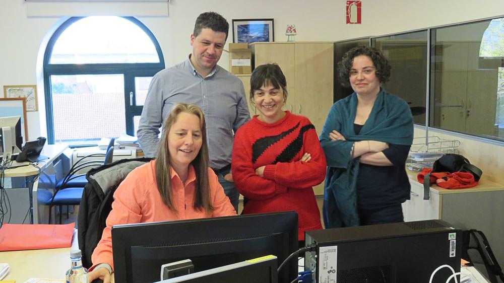 Beate Steger mit Mitarbeitern von Correos, der spanischen Post, sitzend, vor einem PC