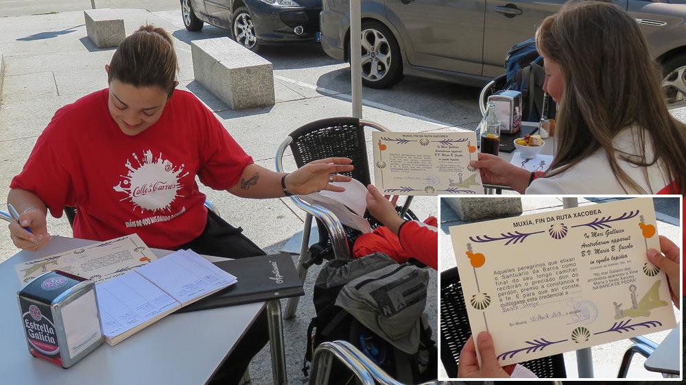 Beate Steger in einem Café in Muxia, eine Frau mit rotem T-Shirt stellt die Muxiana aus.