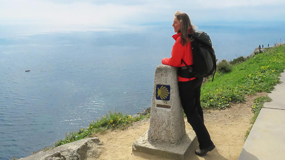 Beate Steger mit roter Jacke und leichtem Rucksack lehnt am Stein in Finisterre mit Blick aufs Meer