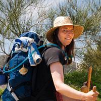 Beate Steger mit blauem Rucksack, Pilgerstab, Hut und Jakobsmuschel