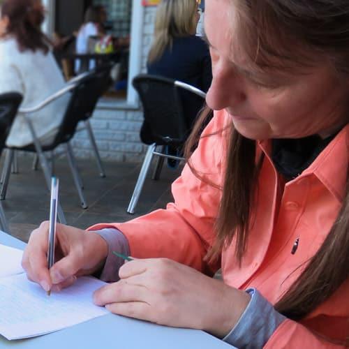 In roter Bluse schreibt Beate Steger ins Tagebuch in einem Café