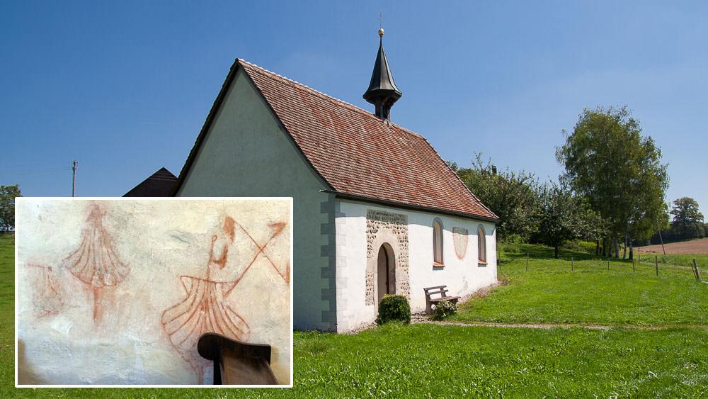 Kapelle auf gründer Wiese, unten links Rötelmalereien mit der Jakobsmuschel
