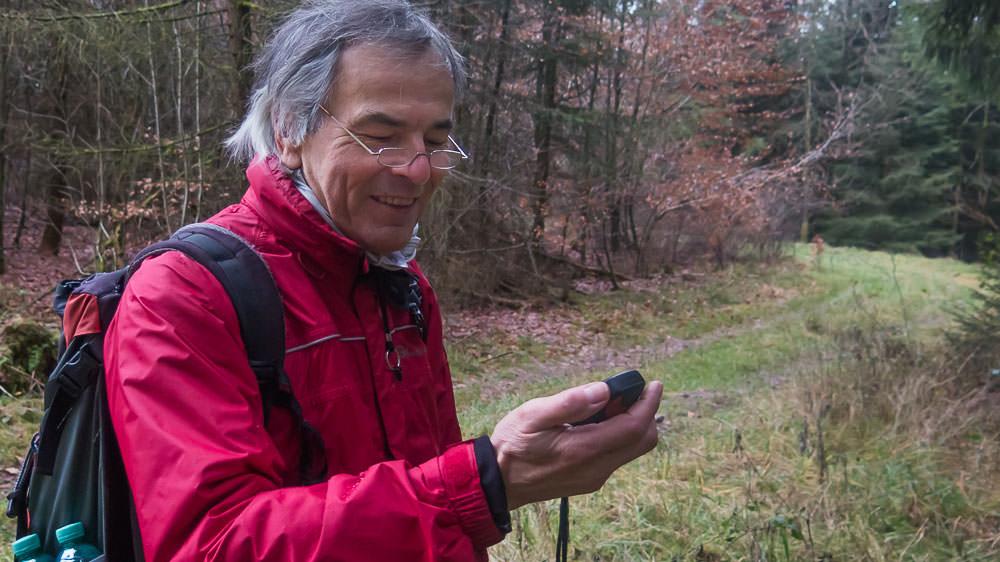 Hans-Jörg schaut auf sein GPS-Gerät in einem Waldstück, dahinter ein Waldweg