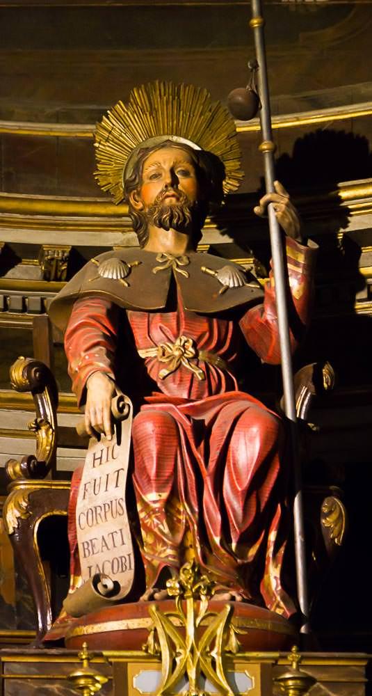 Jakobsstatue mit rotem Mantel, Pilgerstab, eine Papierrolle sowie Umhang mit Jakobsmuscheln
