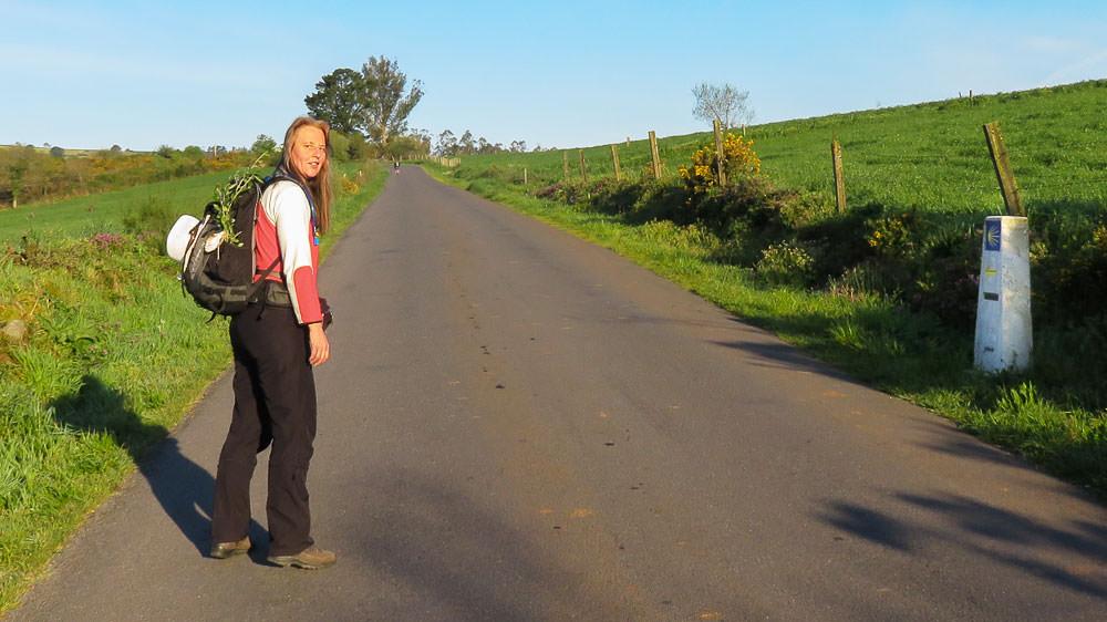 Beate Steger mit Rucksack und Palmwedel wegen Ostern auf asphaltiertem Weg mit Wegzeichen in der Morgensonne
