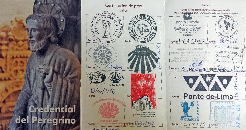 aufgeklappter Pilgerausweis mit Stempeln und Jakobusfigur auf dem Titelblatt