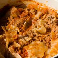 Weißkohl geschichtet mit dem Rouladenteig im Topf in Tomatensauce