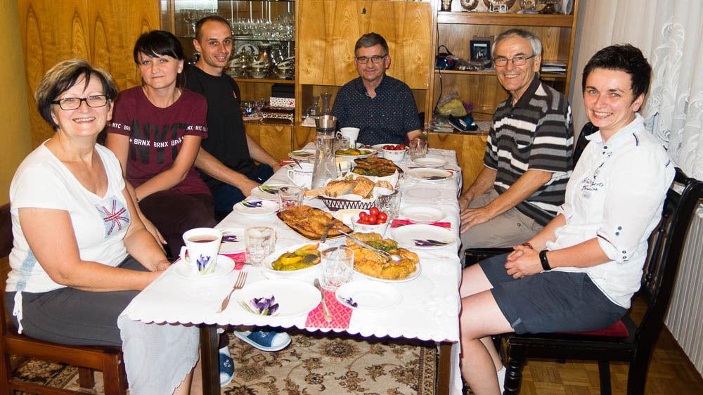 Sechs lächelnde Menschen am Abendbrot-Tisch
