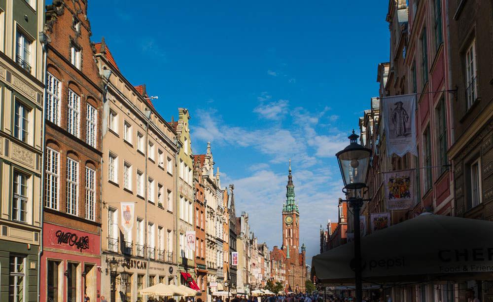 Bunt restaurierte Häuser in der Altstadt von Danzig mit prominentem Gebäude am Ende der Straße