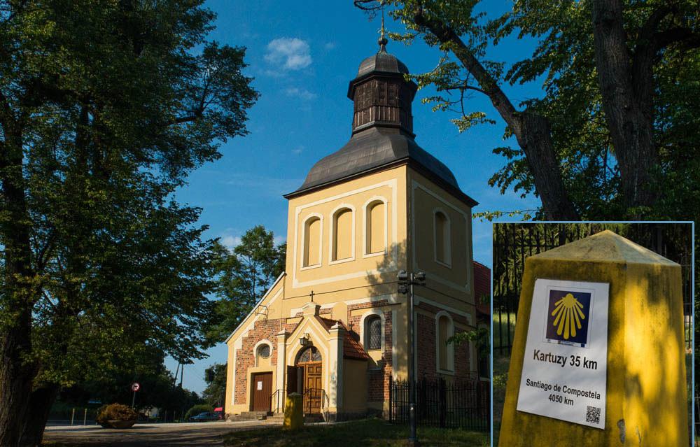 Kirche mit gelber Fassade und Meilenstein auch in gelb mit der Angabe 4050 km nach Santiago de Compostela