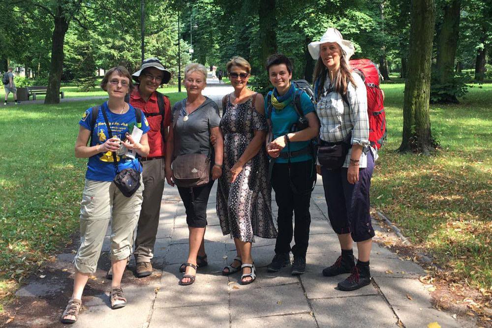 Pilgergruppe aus sechs Personen, in einem Park vor Oliwa, frontal in die Kamera schauend