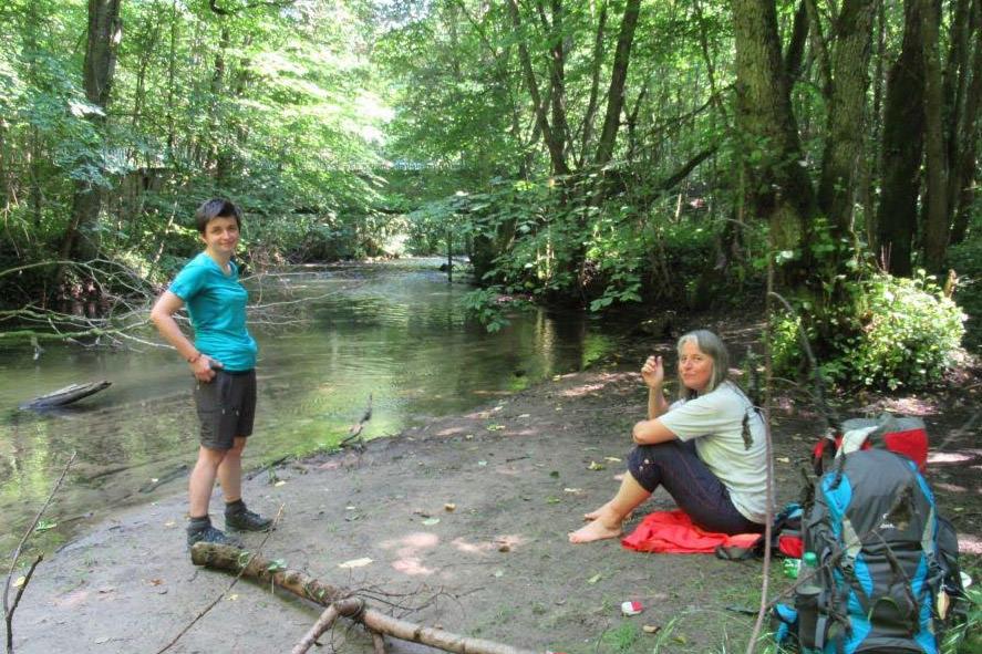 Doro stehend und Beate sitzend am Fluss machen eine Pause