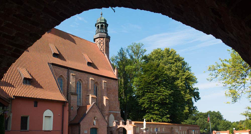 Kirche fotografiert durch einen Torbogen, mit blauem Himmel und großen Bäumen