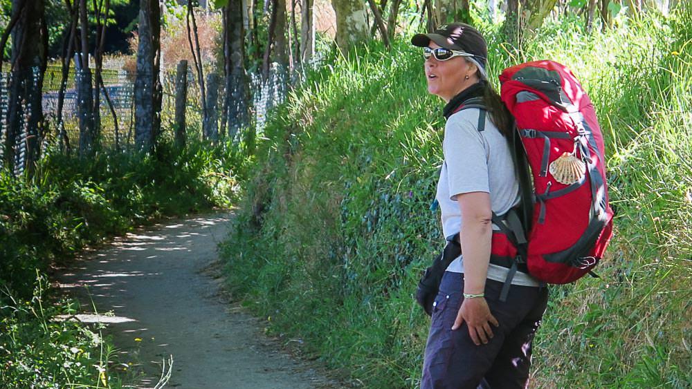 Beate Steger 2016 auf einem engen Weg mit viel Gras, kurz vor Santiago, trägt einen roten Rucksack